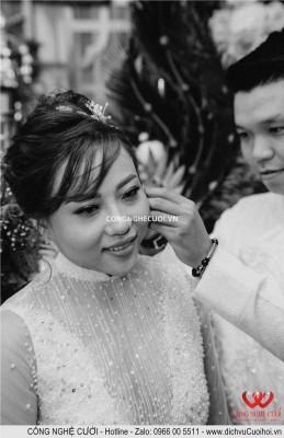 Mẹ chú rể đeo bông tay cho cô dâu và được chú rể hổ trợ