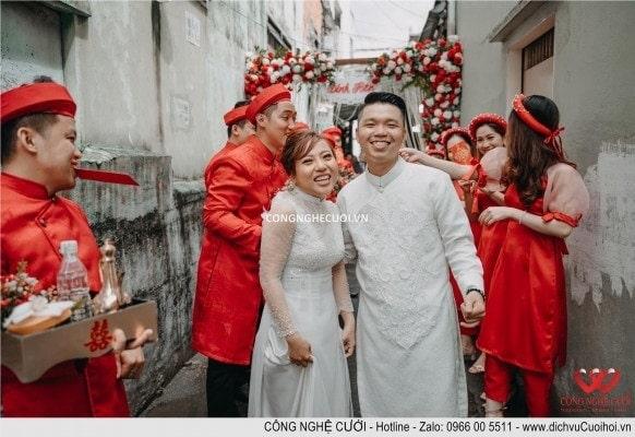 Cô dâu chú rể cùng phát bao lì xì đỏ cho đội bưng quả