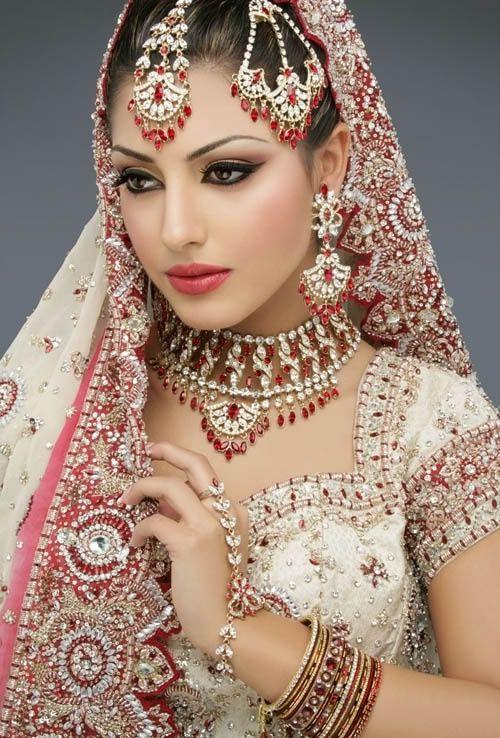 [Caption]Trong văn hóa Ấn Độ, váy cưới truyền thống của cô dâu thường là màu hồng hoặc màu đỏ. Theo phong tục Solah Shringar, trang phục cưới sẽ thường đi kèm theo 16 phụ kiện và đồ trang sức. Ngoài ra, cô dâu vùng phía Bắc Ấn Độ còn có phong tục chấm đỏ giữa trán (gọi là bindi) khi về nhà chồng.