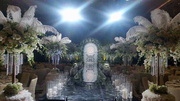 [Caption]Lối đi huyền ảo với những trụ hoa lớn cắm lông vũ và hàng nến phản chiếu lung linh trên nền gương đen tuyền.