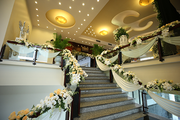 [Caption]Ngay từ cầu thang sảnh tầng 1 là đường dẫn hoa với nến lung linh , cầu thang lối lên sảnh chính được phủ kín hoa tông màu trắng kem ấm cúng và sang trọng.