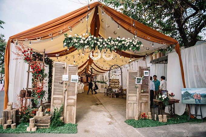 [Caption] Cổng hoa được thiết kế bằng bốn cánh cửa mộc mạc, đính kết hoa artiso. Yếu tố chủ đạo làm nên ý nghĩa cũng như không gian của lễ cưới chính là biểu tượng Horseshoe (Móng ngựa).