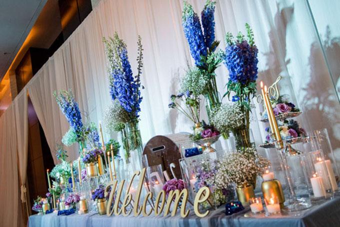 [Caption]Tuy nhiên vì ở Việt Nam có rất ít loại hoa tươi có cùng tông màu này nên đám cưới đã sử dụng rất nhiều hoa nhập khẩu hiếm gặp như Delphinium (giống hoa violet của ta nhưng kích cỡ to hơn), Anemone (thu mẫu đơn), Agapanthus (thanh anh hay huệ sông Nile),...