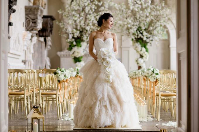 Lấy cảm hứng từ thời trang và nghệ thuật của những năm 1920, váy cưới của Hui có phần thân trên giống phom áo corset, cúp ngực trái tim. Điểm nhấn là phần chân váy được kết từ những chiếc lông đà điểu.