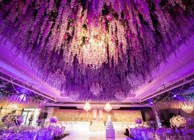 Toàn bộ không gian tiệc cưới hình chữ T được phủ kín bằng hoa, cả trên trần nhà. Tất cả các vật dụng trang trí tạo cho tổng thể sự lộng lẫy nhưng vẫn trang nhã, hài hòa.