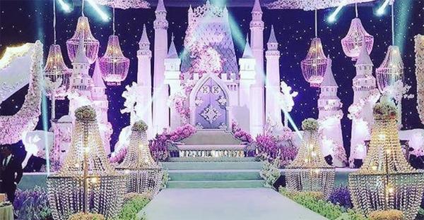 Toàn bộ không gian tiệc cưới được bao trùm bởi sắc hồng, trắng và tím. Sân khấu chính được thiết kế giống một tòa lâu đài, nơi chú rể là hoàng tử sẽ nắm tay cô dâu - công chúa của mình, và nói lời thề nguyền chung sống suốt đời.