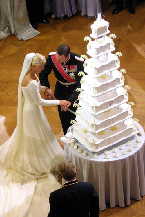 Chiếc bánh cưới trong hôn lễ của hoàng tử Na Uy, Haakon, và công chúa Mette-Marit, cao 7 tầng, màu trắng - vàng. Họa tiết trang trí trên bánh mang đặc trưng phong cách hoàng gia.