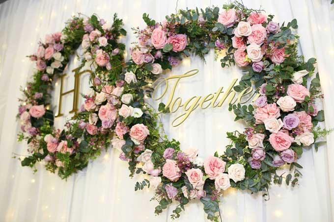 Hai vòng hoa tươi lớn nhất được đặt ở chính giữa, bên trong là tên viết tắt của cô dâu và chú rể (HD), cùng mong muốn mãi mãi bên nhau (Together).