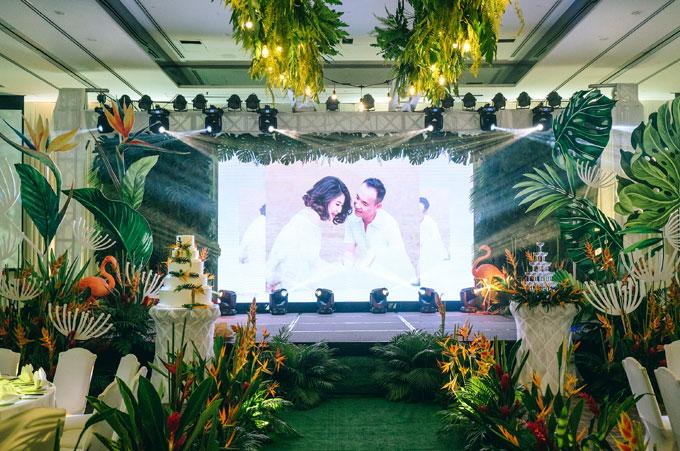 Bên trong phòng tiệc được trang trí thống nhất với sảnh ngoài. Khu vực sân khấu cũng nổi bật với đường hoa trải dài và những chú hồng hạc ở hai bên.